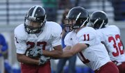 Lawrence High&#39;s Erick Mayo takes a hand-off from quarterback Brad Strauss against Leavenworth on Friday Sept. 23, 2011 in Leavenworth.