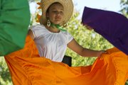 Estrella Zavala, 12, Aurora, Colo., is surrounded by color as she performs a traditional Mexican folklore dance during the annual Festival of Cultures on Sunday, Sept. 25, 2011 at South Park in downtown Lawrence.