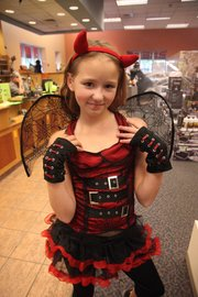 Finding a devilish costume, Shelby Christensen 9, of Shawnee, shows off her find at Halloween Express at 700 N.H. Traditional costumes are big this year — with zombies leading the pack.