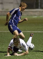 Lawrence High's Justin Riley is tripped up by Olathe East's Conner Elliott. The Lions lost, 1-0, Tuesday, Sept. 27, 2011 at LHS.