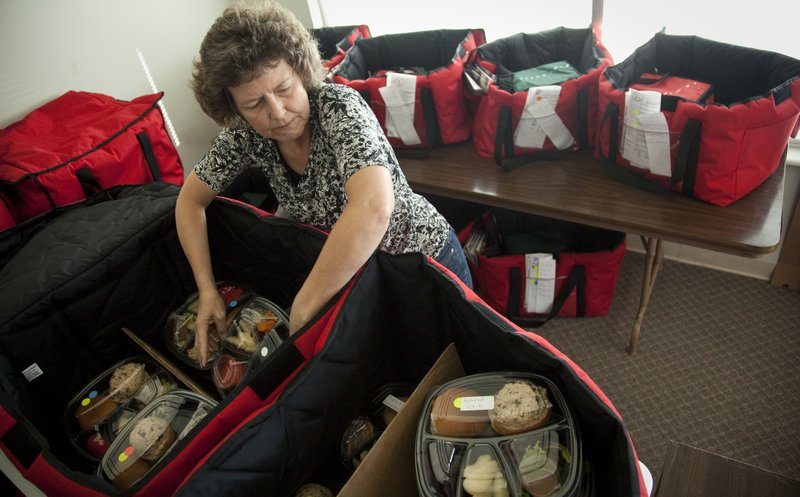 Volunteer Belinda Schuman organizes delivery bags for Meals on Wheels drivers on Tuesday, Sept. 27, 2011, at the service's new office, 2121 Kasold Drive.
