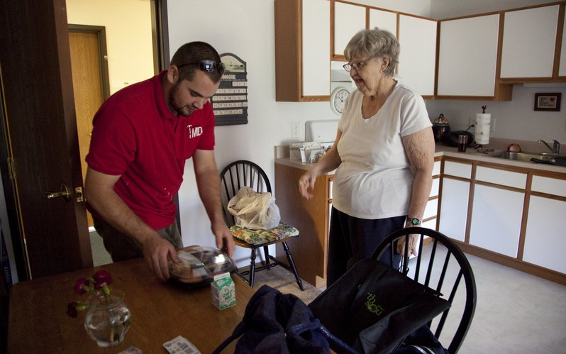 Meals On Wheels volunteer Jacob McCleary sets a lunch down on the kitchen table for recipient Mary Canfield during a delivery on Tuesday, Sept. 27, 2011, in her home at Wyndham Place, 2551 Crossgate Drive.