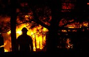 A firefighter watches the flames of a fully-involved house fire at 1439 North 1900 Road as crew respond around 4 a.m. Thursday, Sept. 29, 2011.