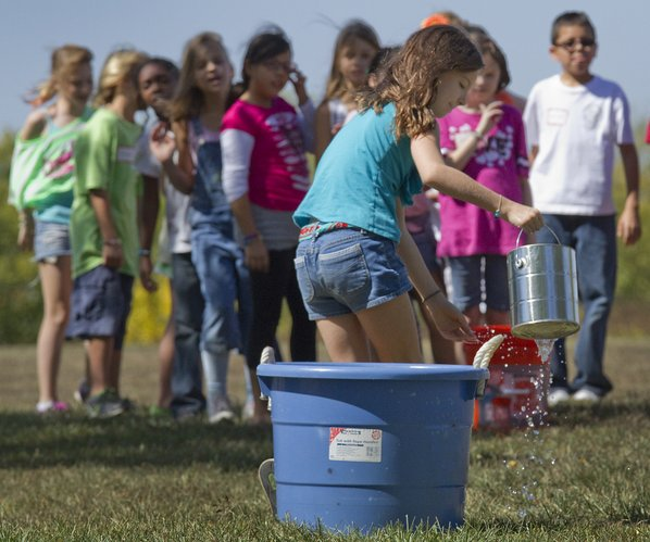 Ava Greene, center, carefully carries back her bucket of water In a relay exercise with other students from Cordley Elementary School to see how much water pioneers used in a day.  Students from area schools learned a little bit about protecting water Thursday at the 4th Grade Water Festival at Clinton Lake Overlook Park.