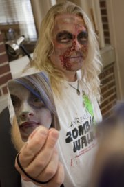 "Harold Agnew holds a mirror so his daughter, Parvaneh Karch-Agnew, can see the ""zombie face"" that makeup artist Elahe Marjovi painted on her. Marjovi also did makeup on Agnew, the organizer of this year&squot;s Lawrence Zombie Walk. The walk takes place on Thursday, Oct. 6, and benefits the Lawrence Humane Society."