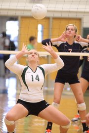 Free State junior Ashley Powers gets under a set before Olathe East freshman Lindsey Benson on Thursday, Sept. 29, 2011 at Free State High School.