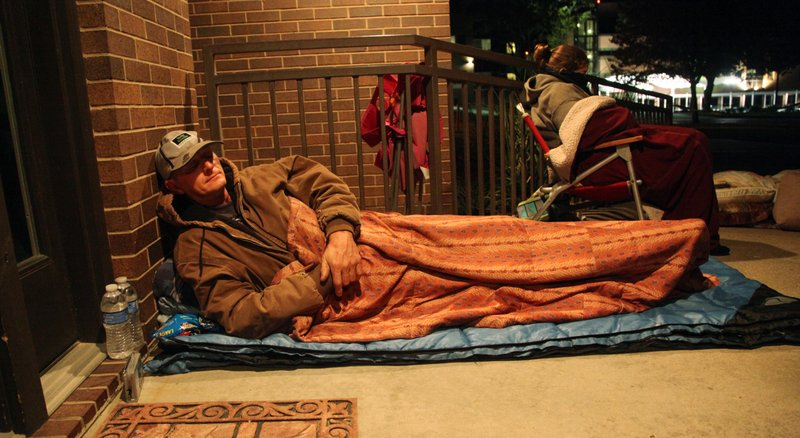Billy Mason catches some sleep about 6 a.m. Friday, Sept. 30, 2011, while he waits in line to receive free dental services at the Douglas County Dental Clinic, 316 Maine. The clinic offers a Free Dental Day once a year for low-income, uninsured residents, and the services are provided on a first-come, first-served basis. The clinic typically is able to help about 70 patients. Each year, the line begins to form earlier with last year's starting about midnight.
