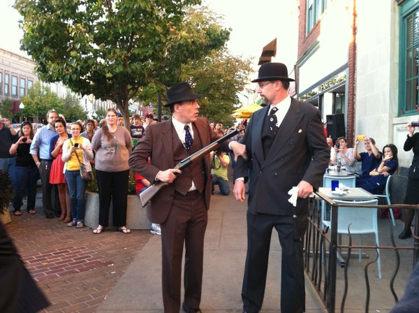 Theatre Lawrence actor Shawn Trimble, left, playing bank robber Clyde Barrow, coerces Lawrence Mayor Aron Cromwell, playing the president of First National Bank, to open the bank vault. The re-enactment Friday of a supposed 1932 robbery began at the Eldridge hotel and progressed to Teller's, 746 Mass.
