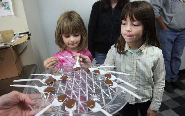 Twin sisters, from left, Allison 6, and Cecellia  6, Jakubauskas, both of Lawrence, get ready to lick up some chocolate at Sleepy Jeans Confections during the Annual Kaw Vally Farm tour was held on Saturday Oct 2, 2011, as area farms showed of their talents.