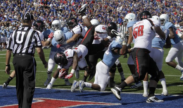 Texas Tech running back Eric Stephens (24) jumps over KU's defensive line for a touchdown during the second half Saturday, Oct. 1, 2011, at Memorial Stadium.