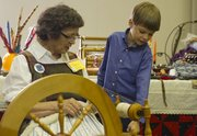 Six-year-old Karsten Hunstad, Lee's Summit, Mo., listens as Regina Shaver, Lawrence, explains how her spinning wheel works during the 2011 Nordic Heritage Festival.