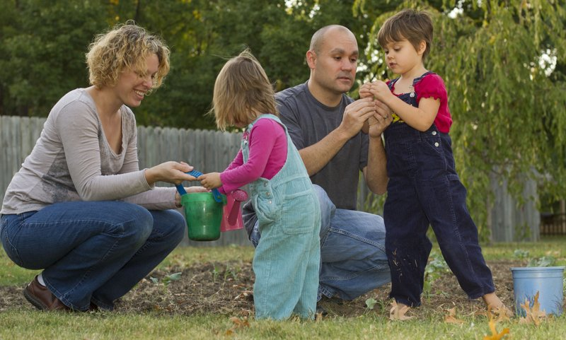 Sesha Edie, 5, right, shows her father Brian something she found while playing in the garden while Jessica, left, helps Mira, 2, with a water bucket. Brian is an organizer of the Homegrown Lawrence Festival, Oct. 14. Part of his inspiration for working on the festival, which raises funds to start school gardens, is that Secha will start at public school next year.