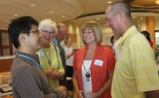 Kenichi Arai, from Hiratsuka, Japan, left, is greeted by Sue Hack and Kathy and Dick Stuntz during a reception at the Spring Hill Suites on Monday. A 13-member delegation from Hiratsuka, one of Lawrence's sister cities, arrived in Lawrence on Monday and included Hiratsuka Mayor Katsuhiro Ochiai.