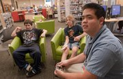 "Philip Fukuto, foreground right, youth services assistant at Lawrence Public Library, 707 Vt., and a skilled video game player, provides lessons on the game ""Super Smash Bros. Brawl,"" on Oct. 5. From left are Alejandro Esparza, 12, and Nathan Fletchall, 12."