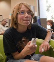 "Nathan Fletchall, 12, concentrates on a game of ""Super Smash Bros. Brawl,"" on Oct. 5 at the Lawrence Public Library, 707 Vt. The library plays host to a teen video game tournament once a month."