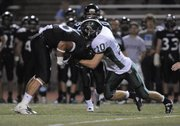 Free State senior Calloway Schmidt (10) puts the stop on Lancer wide receiver Elliot Faerber as Free State played Shawnee Mission East Thursday, Oct. 6, 2011, in Overland Park.