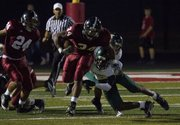 Lawrence High running back Tyrone Jenkins (34) evades a tackle by Shawnee Mission South's Alterick Buchanon on Friday, Oct. 7, 2011 at LHS.