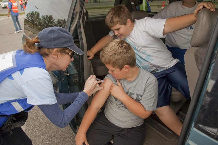Sitting on the step of the family van, Evan Liakos, 8, gets his flu shot from volunteer Nola Bienoff under the watchful eye of his twin brother Conner. Evan received a free flu shot during a drive-thru flu shot clinic Saturday, Oct. 8, 2011, that was organized by the Lawrence-Douglas County Health Department.