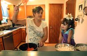 Aniela Kiekel slowly drips some melted marshmallows together to make popcorn balls with her daughter, Shasta, 3. Kiekel says Shasta enjoys helping to make chocolate cake.