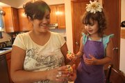 Aniela Kiekel and her daughter, Shasta, 3, enjoy putting together a sticky treat — popcorn balls. Kiekel says she measures out the ingredients and lets Shasta add them in. Popcorn balls are a mixture of popcorn, marshmallows, butter and food coloring.