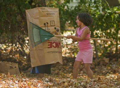 Turner Omelau, 7, left, hides inside a compost bag from his friend Taloa Lena, 6, as the two raked and played in the leaves in front of their houses in East Lawrence, Saturday, Oct. 8, 2011. The city is encouraging people to compost or mulch leaves rather than burn them or put them in the trash.