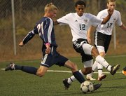 Free State senior Trevor Vanahill fights for possession with Olathe East's Bryan Jones on Tuesday, Oct. 11, 2011 at FSHS.