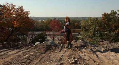 Holli Joyce, stands on the edge of a Kansas City property that borders Interstate 70. Once a 1900s rock quarry, the property is now the site of a clean fill project, which accepts demolition debris with the hope of reusing the material.