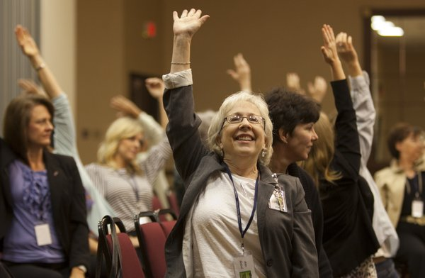 Ann Gabel, director of education and learning services at Lawrence Memorial Hospital smiles her way through a series of stretching exercises during the first WorkWell Lawrence Symposium on Wednesday, Oct. 12, 2011, at the Holiday Inn Lawrence, 200 McDonald Drive. Gabel and other professionals listened to speakers tell stories of their efforts to help create a healthier workplace.