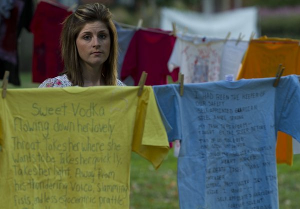 Rebecca Delaney stands between rows of T-shirts that are part of The Clothesline Project during &quot;Take Back The Night&quot; held Thursday, Oct 13, 2011, in South Park. Delaney, who is a survivor of domestic violence, was a keynote speaker during the event.