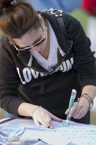 Jennifer Corral, Wichita, draws a flower on a shirt that is part of The Clothesline Project during &quot;Take Back The Night&quot; held Thursday, Oct 13, 2011, in South Park. The Clothesline Project, which begin in 1990, is a way for women affected by violence to express their emotions by decorating a shirt. 