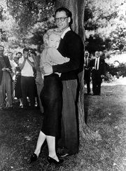 Actress Marilyn Monroe poses with playwright Arthur Miller in 1956, wearing a pencil skirt.