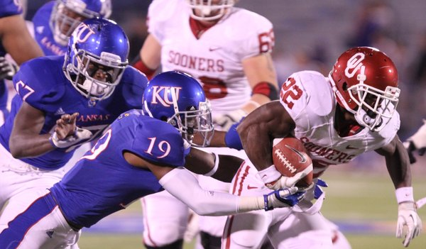 Kansas cornerback Isiah Barfield can't strip the ball from Oklahoma running back Roy Finch as he heads deep in Jayhawk territory during the third quarter on Saturday, Oct. 15, 2011 at Kivisto Field.