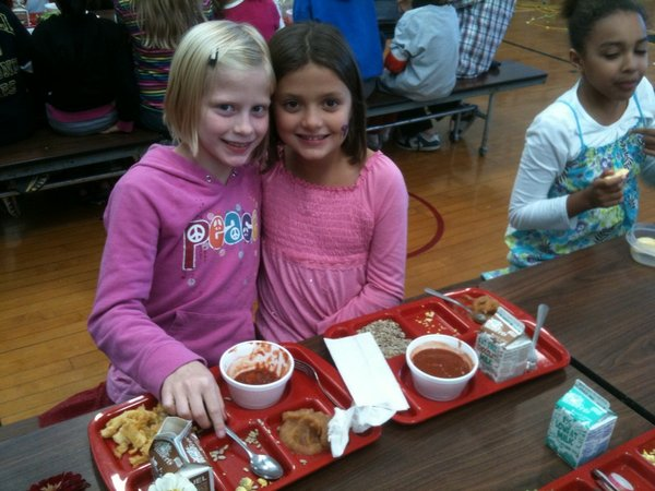 Mally Nowlin, left, and Calah Hunt, both third-graders at Cordley School, enjoy the fall flavors of their locally-grown and locally-produced lunches. The girls said they really liked the homemade applesauce.