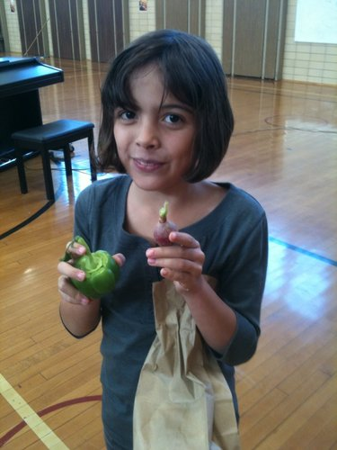 Mikah Beaty, a third-grader at Cordley School, holds up the pepper and radish that she received from the Leavenworth Penitentiary Community Service Farm.