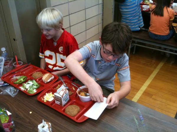 Wheeler Battaglia-Davis, left, and Jackson Rogers dig into their locally-grown and locally-produced lunches at Cordley School on Wednesday, Oct. 19, 2011. Rogers picked tomatoes at a local farm that were served on the salad bar.