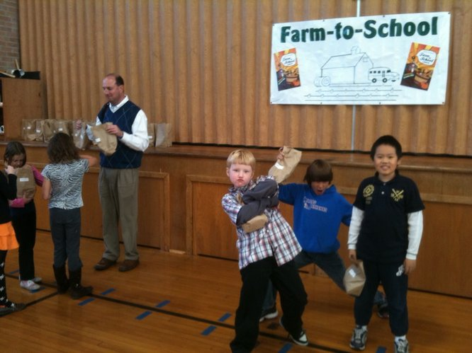 Cordley School third-graders, from left, Guthrie Bricker, George Dobson and Patrick Soo pose for a photo after eating a lunch of locally-grown and locally-produced foods. At left, Principal Scott Cinnamon hands out small bags of produce to students to take home. The produce donated by the Leavenworth Penitentiary Community Service Farm.