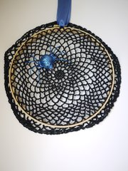 A crocheted doily stretched on an embroidery hoop is a nearly instant Halloween decoration.