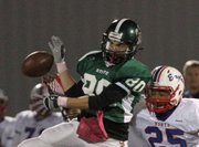 Free State's Sam Hearnen goes up for a pass in the first half against Olathe North's Hanson Chase on Friday, Oct. 21, 2011.