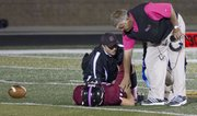 Lawrence High head coach Dirk Wedd offers his support to injured player Brad Strauss during the Lions' game against Olathe Northwest on Friday, Oct. 21, 2011 at LHS.
