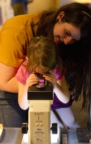 "Graduate student Carla Harper lifts 4-year-old Erika Josling, Oskaloosa, up to a dissection scope so she can see fossilized ferns up close during the ""What on Earth? Rocks, Fossils and Meteorites"" event Sunday at Kansas University's Natural History Museum."