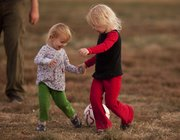Sisters Amalie Stone, 2, left, and Eva Stone try to take away the ball from each other.