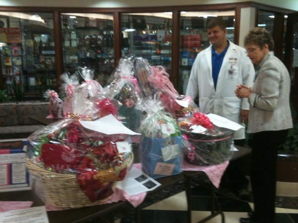 Pharmacist Paul Pierce and Paula Dupigny-Leigh, a registered nurse, look over gift baskets Wednesday in the lobby at Lawrence Memorial Hospital. For a small donation, individuals can be entered in a drawing for the chance to win a a gift basket as part of the 2011 Stepping Out Against Breast Cancer dance. The winners will be announced at Saturday's dance.