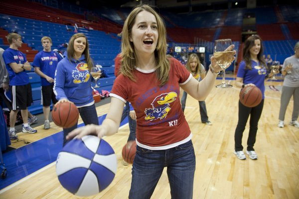 "Tami Radohl, a KU graduate from Olathe, tries to manage dribbling the ball and drinking wine in Allen Fieldhouse Thursday, Oct. 27, 2011, during ""Ladies Night Out with Bill Self."""