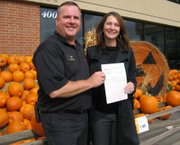 Marty Streit, store manager for Hy-Vee, 4000 W. Sixth., presents a $10,000 check to Susan Esau, executive director of the Lawrence Schools Foundation. The money is a donation made by the company through its Dollars for Scholars Program. Streit presented the check Oct. 17, 2011, outside the store.