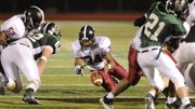 Lawrence High's Tyrone Jenkins falls on a fumble in the second half against Free State on Friday, Oct. 24, 2011.
