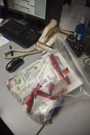 A ziplock bag holds smaller bags of cash that is waiting to be counted in the evidence room.