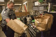 Officer Michael Ramsey processes items that were found in a stolen car. He had to use a roller storage cabinet for a work surface in the garage under the Judicial and Law Enforcement Center.