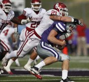 Kansas State quarterback Collin Klein (7) is sacked by Oklahoma linebacker Tom Wort (21) during the first half Saturday, Oct. 29, 2011, in Manhattan, Kan.
