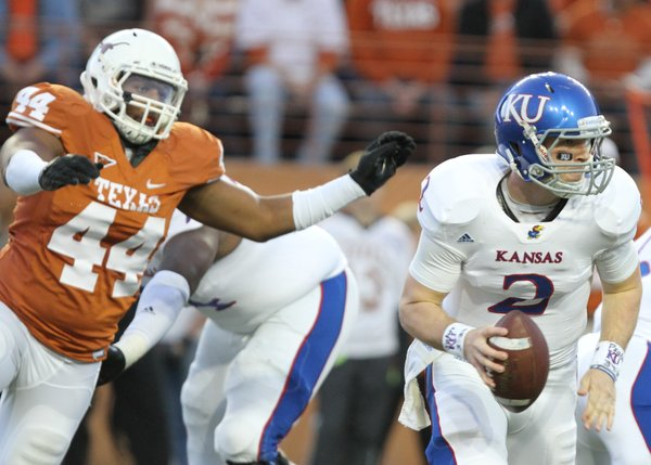 Kansas quarterback Jordan Webb scurries away from Texas defensive end Jackson Jeffcoat during the first quarter on Saturday, Oct. 29, 2011 at Darrell K Royal-Texas Memorial Stadium.