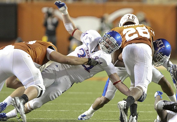 Kansas linebacker Huldon Tharp (34) and Bradley McDougald try to bring down Texas running back Malcolm Brown during the third quarter on Saturday, Oct. 29, 2011 at Darrell K Royal-Texas Memorial Stadium.